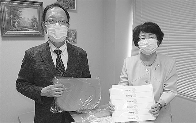 竹内一浩医師会会長(左)にフェイスシールドを手渡す松本会長